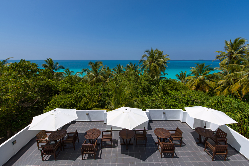Boutique Beach Hotel Roof Terrace with Tables, Chairs, White Umbrellas and Azure Blue Ocean in the Background